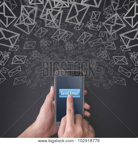 Finger pressing send email button on smartphone on chalkboard background poster