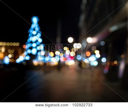 Christmas tree in the city square. Abstract dark blurry urban background.