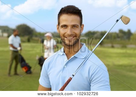 Closeup portrait of handsome young male golfer with golf club.