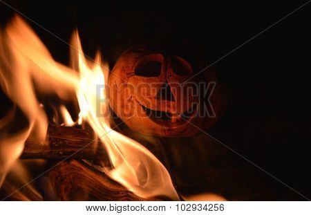 Candlestick pumpkin and bonfire in the dark, symbol of Halloween