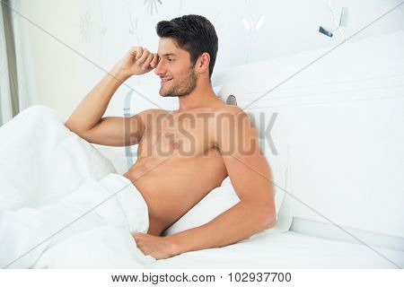 Portrait of a handsome man talking on the phone in the bed at home