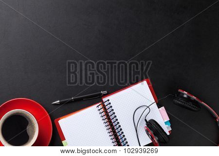 Office leather desk with notepad, coffee cup and headphones. Top view with copy space poster