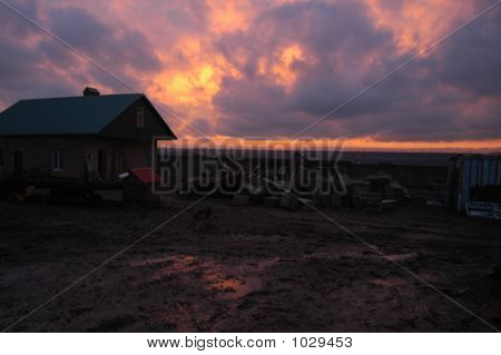 sunset on a ukrainian farm with reflection of the fiery sky in the muddy foreground