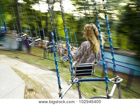 Young beautiful girl rides on a swing suspended on chains.Motion blur