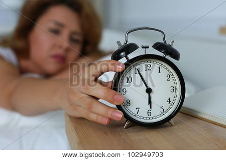 Young sleepy woman trying to turn off the alarm clock. Early morning waking up. poster