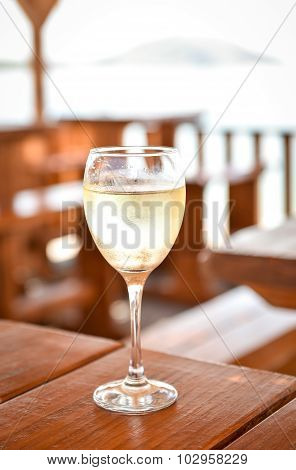 Glas Of Cold White Wine On A Wooden Table.