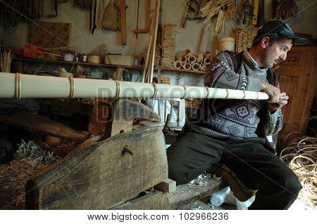 Carpenter Handcrafting A Wooden Alpenhorn