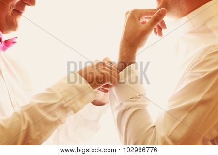 Groom's men helping the groom with his cuff links