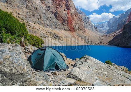 Lonely tent stands on the shore of a beautiful mountain lake