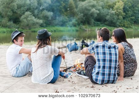 Four Adult Friends Sitting At Bonfire On Sandy Beach