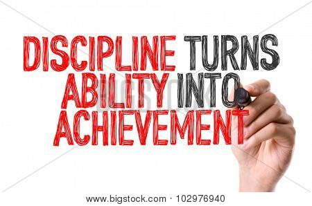 Hand with marker writing: Discipline Turns Ability Into Achievement