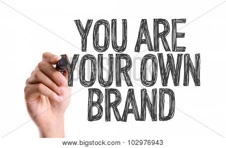 Hand with marker writing: You Are Your Own Brand