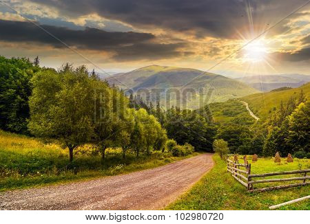 Fence Near Road Down The Hill With  Forest In Mountains At Sunset