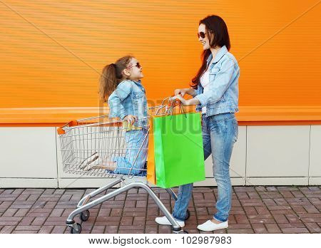 Happy Family Smiling Mother And Child With Trolley Cart And Colorful Shopping Bags