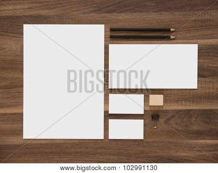 Letterhead, envelope and blank business cards on wooden desk.
