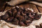 Whole dried Cola Nuts (close-up shot) on wooden background poster