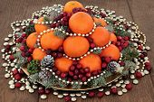 Christmas satsuma orange and cranberry fruit, gold bead and smartie decorations, holly, mistletoe and winter greenery over oak background. poster