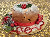 Panettone cake with merry christmas ribbon, holly, mistletoe, decorations and winter greenery over oak background with gold stars. poster