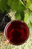 Glass of refreshing mulberry juice with berries on table close up poster