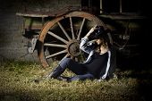 color image of a beautiful young woman casually dressed in boots, jeans and denim shirt with hat, leaning against the wheel of an old rustic wooden wagon in a brick barn in a farm setting poster
