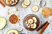 raw vegan avocado banana chocolate pudding on a wooden table poster