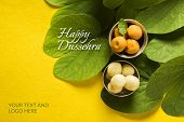 indian festival dussehra, showing golden leaf with traditional indian sweets pedha in silver bowl on yellow background, greeting card poster