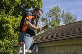 Contractor on ladder with cell phone figuring out hail damage repair costs for customer. poster