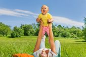 Happy mother lifting her baby up with straight arms while laying on the green grass in park during summer poster