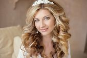 Healthy hair. Wedding makeup. Beautiful smiling girl bride with long blonde curly hairstyle. bridal indoor portrait. poster