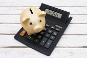 Saving for your retirement A golden piggy bank on a calculator with word Roth over a distressed wood background poster