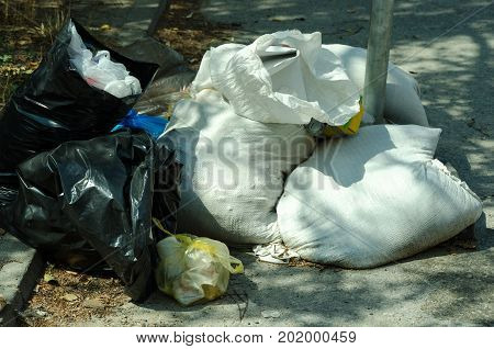 Garbage bags full of litter polluting the street in the city