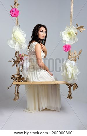 Smiling bride on seesaw in studio. Young brunette woman in wedding dress on seesaw