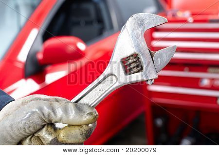Hand with wrench. Mechanic. Auto repair shop. poster