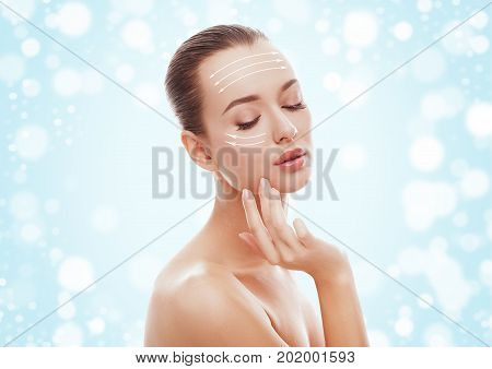 Beautiful young girl touching her face with lifting arrows on blue background and snow. Plastic surgery, facelift and rejuvenation concept. Fashion, holiday, cosmetology, people concept.