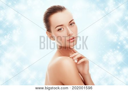 Beautiful young girl touching her face on blue background and snow. Plastic surgery, facelift and rejuvenation concept. Fashion, holiday, cosmetology, people concept. Skincare on winter time.