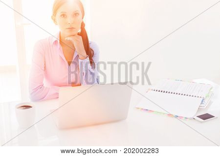 Businesswoman looking bored in front of laptop and television