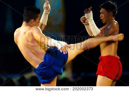 Bangkok Thailand - April 10 2007: Muay Thai kickboxer with wrapped hands kicking a wincing opponent during traditional exhibition kickboxing match at the Grand Palace