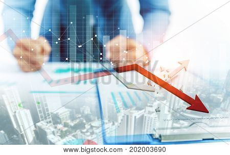 Businessman point at decreasing graph and increasing broken graph with city background
