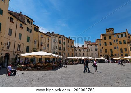 LUCCA, ITALY - MAY 24, 2017: Piazza del Anfiteatro with unidentified people. The ring of buildings surrounding the square, follows the shape of the former 2nd century Roman Amphitheater of Lucca