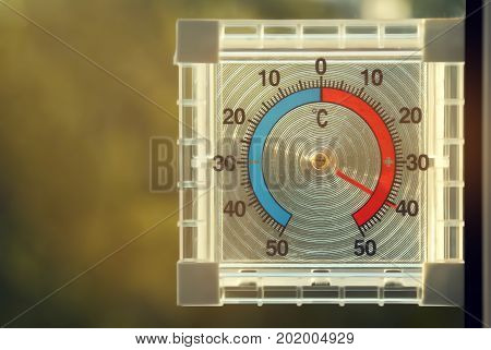 A plastic transparent square thermometer shows a high temperature of 40 degrees Celsius