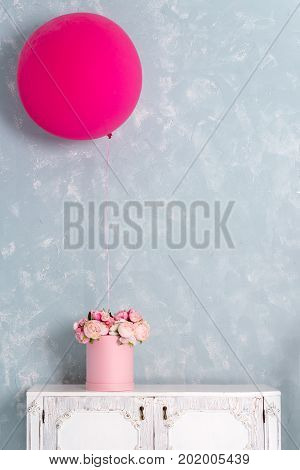 Flowers in round luxury present box and big pink balloon on chest of drawers. Bouquet of pink and white peonies in paper box. Interior decoration in in pastel colors. Free copyspace for text