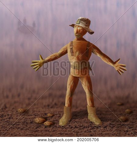 Potato soldier in an armored jacket, hat, with a belt and boots on a potato field