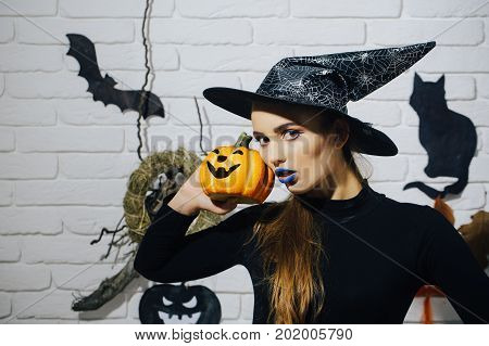 Halloween mystery and horror concept. Woman with blue lips and pumpkin. Holiday celebration symbols on white brick wall. Girl in witch hat and black costume. Jack o lantern.