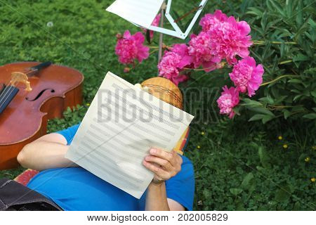Man lying on grass and writing music ideas on music sheets outdoor summertime photo