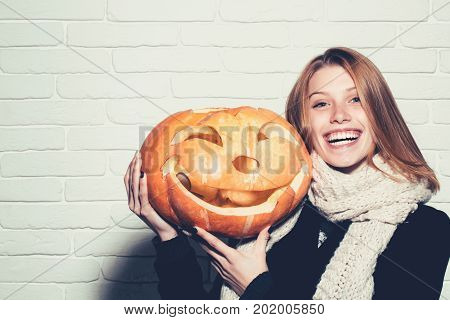 Halloween woman with happy face. Girl with orange scary pumpkin. Woman in coat and scarf at brick wall. Holiday and celebration. Party and traditional food copy space