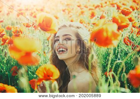 girl with long curly hair hold flower in field of red poppy seed with green stem on natural background summer spring drug and love intoxication opium
