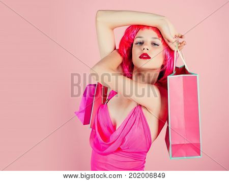 Woman with shopping bags. Girl wearing red wig and fashionable clothes. Sale and black friday. Fashion shopper posing on pink background. Holidays celebration concept copy space