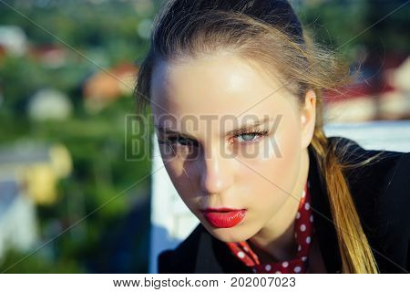 Girl with red lips makeup on face on sunny day. Woman posing on blurred natural landscape. Beauty and youth concept. Summer vacation and wanderlust