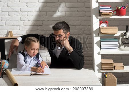 Girl And Her Teacher In Classroom On White Brick Background