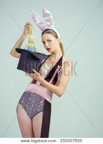 Magic and entertainment. Woman wearing bunny ears. Girl in lingerie on grey background. Magician pulling rabbit toy out of top hat. Hat trick concept.